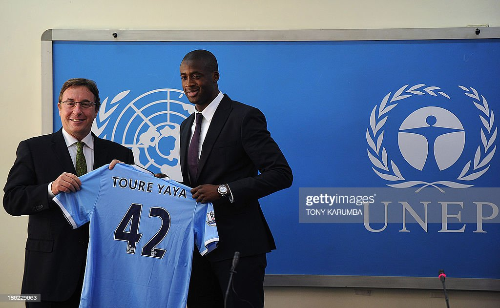 Ivory Coast's football player Yaya Toure (R) gives UNEP executive Director Achim Steiner a signed Manchester City jersey as he was appointed the United Nations Environment Program goodwill ambassador during a press conference at the UNEP headquarters in the Kenyan capital Nairobi on October 29, 2013. Toure, African Footballer of the Year Toure and star of Manchester City, warned that the slaughter of elephants for their ivory was threatening their very existence as he was appointed UNEP ambassador.