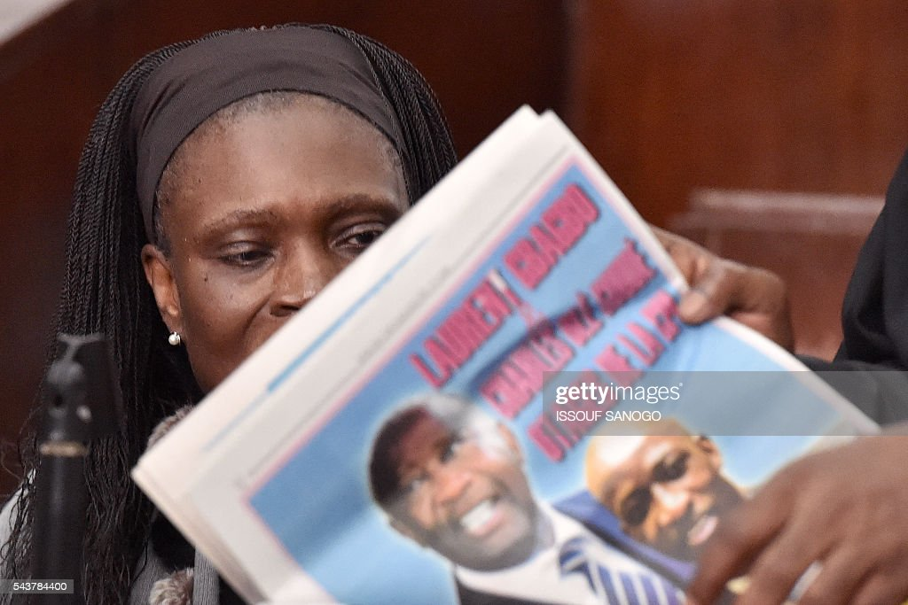 Ivory Coast's former first lady Simone Gbagbo looks at a newspaper as she attends her trial on June 30, 2016 at the appeal court in Abidjan. An ex-militia chief in Ivory Coast said on June 27, 2016 at the trial of Simone Gbagbo for crimes against humanity that the former first lady had financed the movement. Simone Gbagbo faces allegations of crimes against prisoners of war, crimes against the civilian population and crimes against humanity. / AFP / ISSOUF