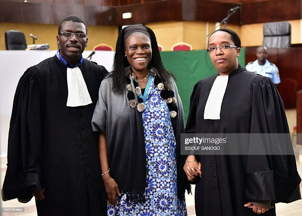 Ivory Coast's former first lady Simone Gbagbo (C) poses with lawyers Habiba Toure (R) and Ange Rodrigue Dadje (L) as she attends her trial on June 30, 2016 at the appeal court in Abidjan. An ex-militia chief in Ivory Coast said on June 27, 2016 at the trial of Simone Gbagbo for crimes against humanity that the former first lady had financed the movement. Simone Gbagbo faces allegations of crimes against prisoners of war, crimes against the civilian population and crimes against humanity. / AFP / ISSOUF