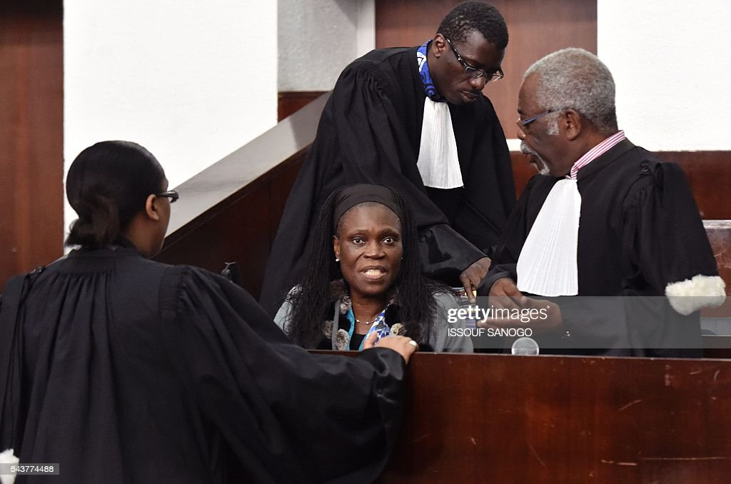 Ivory Coast's former first lady Simone Gbagbo speak with her lawyers during her trial on June 30, 2016 at the appeal court in Abidjan. An ex-militia chief in Ivory Coast said on June 27, 2016 at the trial of Simone Gbagbo for crimes against humanity that the former first lady had financed the movement. Simone Gbagbo faces allegations of crimes against prisoners of war, crimes against the civilian population and crimes against humanity. / AFP / ISSOUF