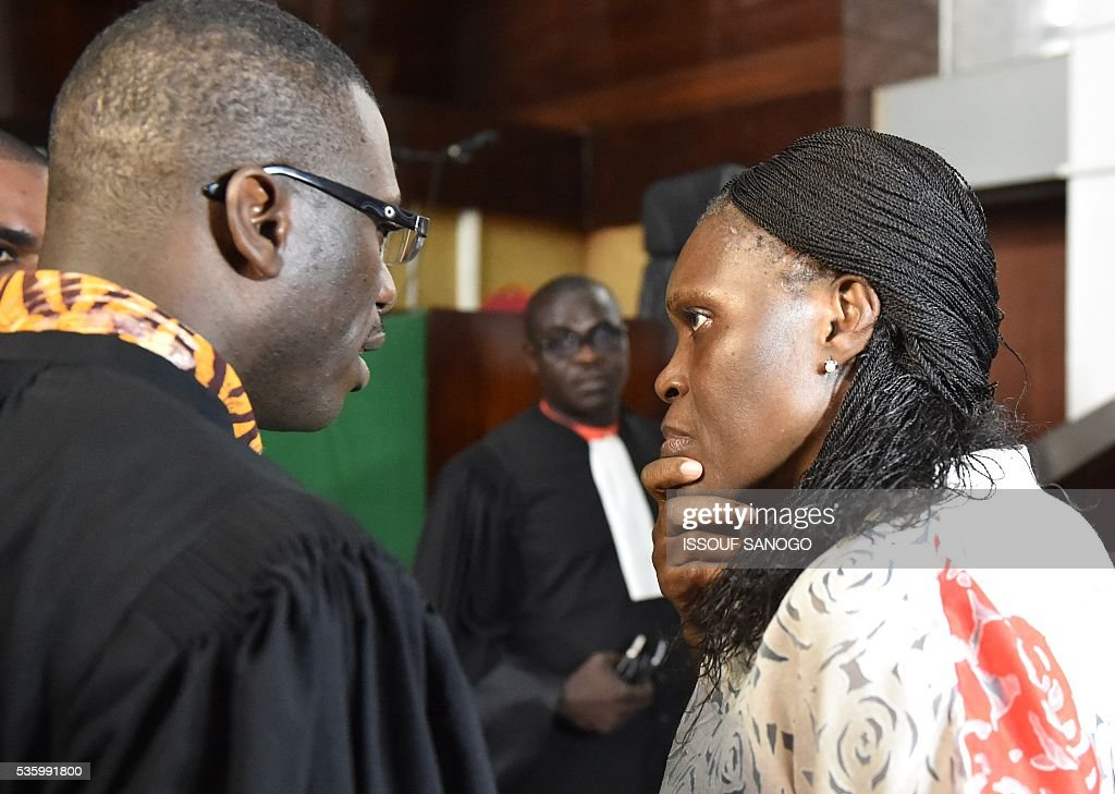 Ivory Coast's former first lady Simone Gbagbo (R) speaks with a lawyer during her trial at the Abidjan Justice Court on May 31, 2016. Simone Gbagbo goes on trial for crimes against humanity in what many see as a litmus case for justice in the west African country. The hearings into the 66-year-old's role in post-election carnage in 2010 is expected to last a month with 32 witnesses testifying. SANOGO