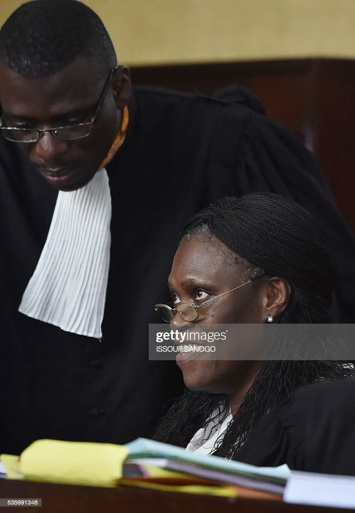 Ivory Coast's former first lady Simone Gbagbo speaks with her lawyer during her trial at the Abidjan Justice Court on May 31, 2016. Simone Gbagbo goes on trial for crimes against humanity in what many see as a litmus case for justice in the west African country. The hearings into the 66-year-old's role in post-election carnage in 2010 is expected to last a month with 32 witnesses testifying. SANOGO