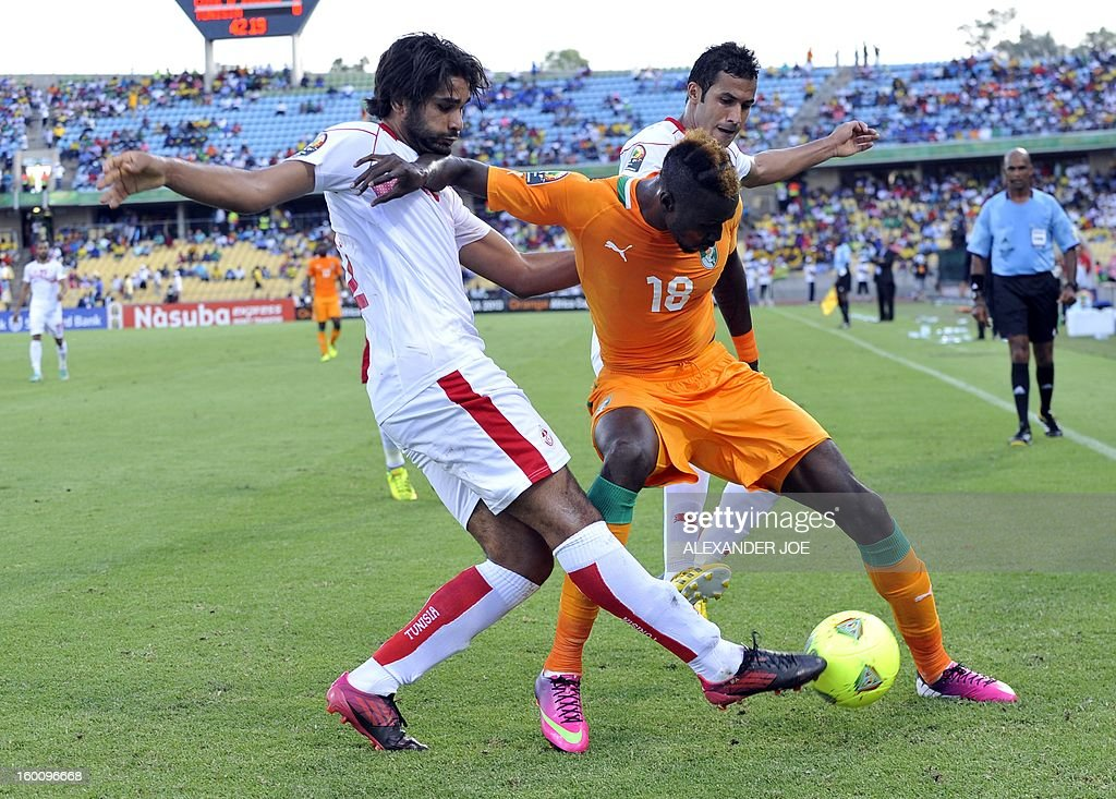 Ivory Coast's forward Lacina Traore (C) figthts for the ball with Tunisia's midfielder Oussama Darragi during the 2013 African Cup of Nations football match Ivory Coast vs Tunisia in Rustenburg on January 26, 2013 at Royal Bafokeng Stadium in a Group D match. Ivory Coast won 3-0.