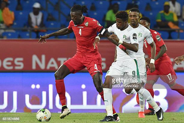 Ivory Coast's forward Wilfred Zaha challenges Togo's forward Emmanuel Adebayor during the 2017 Africa Cup of Nations group C football match between...