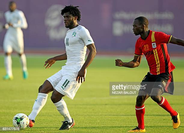 Ivory Coast's Franck Kessie passes the ball as he is marked by Uganda's Mike Azira during the friendly football match between Ivory Coast and Uganda...