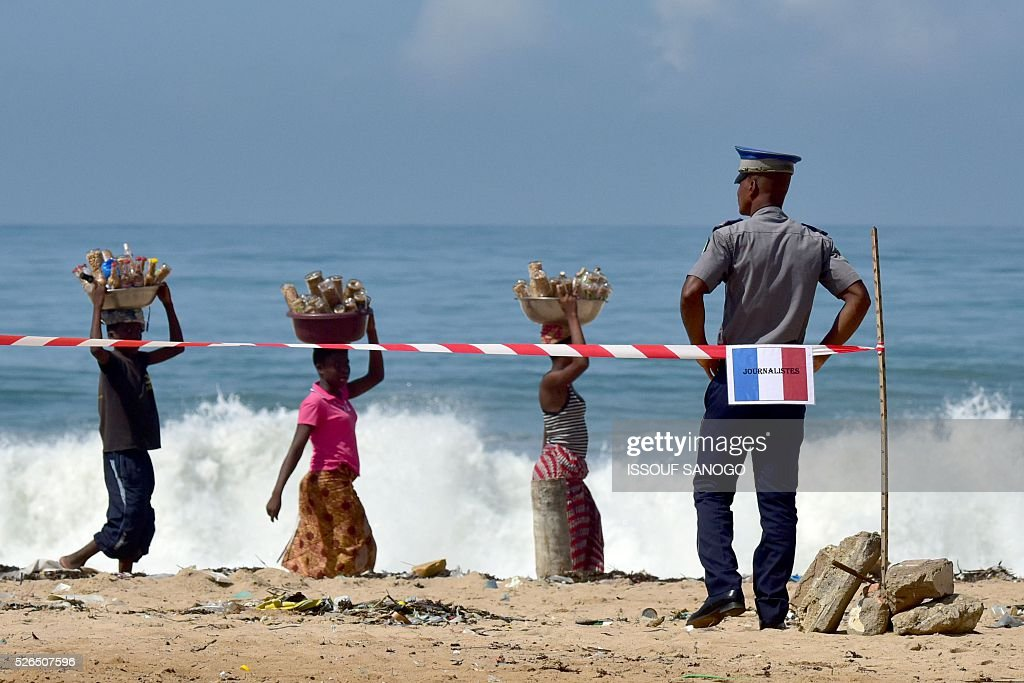 A Ivory Coast's gendarme looks at people walking past him on the beach on April 30, 2016, before the arrival of French Defence Minister Jean-Yves Le Drian at the Grand-Bassam beach by the Hotel Etoile du Sud to pay a tribute to the 19 victims of the jihadist attack of March 13. France will increase the number of its troops in Ivory Coast, Defence Minister Jean-Yves Le Drian said on April 29 on a trip to the African nation which hosts a regional base for French forces. / AFP / ISSOUF