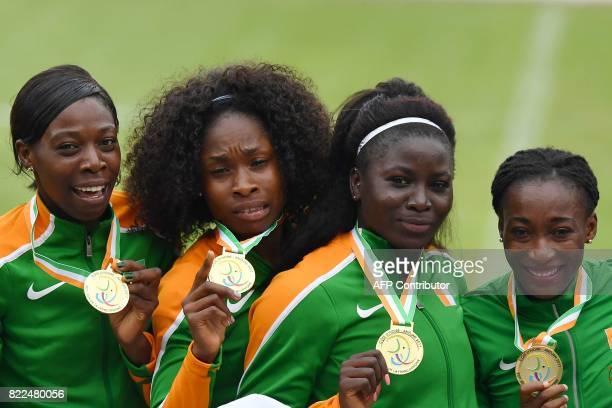 Ivory Coast's Karel Elodie Ziketh Mireille Parfaite Gaha Adeline Gouenon Nanzie and Marie Josee Ta Lou celebrate on the podium after winning the...
