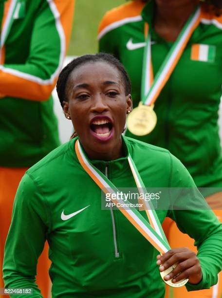 Ivory Coast's Marie Josee Ta Lou celebrates on the podium with her team after winning the women's 4x100m relay at the Felix HouphouetBoigny Stadium...