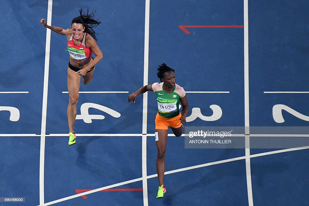 Ivory Coast's MarieJosee Ta Lou crosses the finish line ahead of Bulgaria's Ivet LalovaCollio as they compete in the Women's 200m Semifinal during...