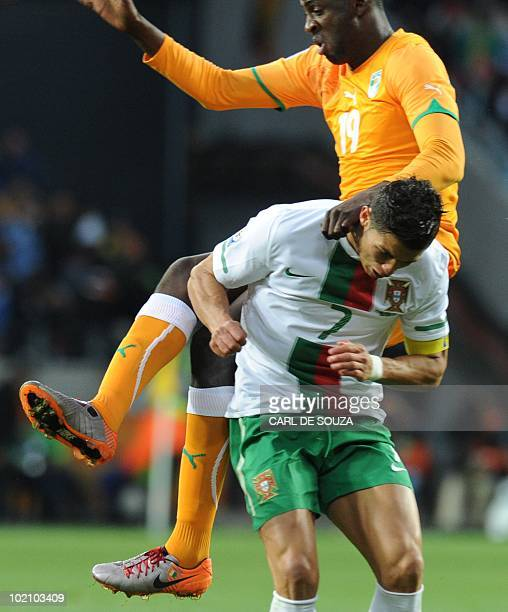 Ivory Coast's midfielder Yaya Toure leans on Portugal's striker Cristiano Ronaldo as he heads the ball during the Group G first round 2010 World Cup...