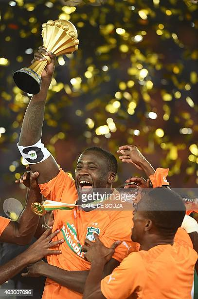 Ivory Coast's midfielder Yaya Toure raises the trophy as he celebrates with teammates after winning the 2015 African Cup of Nations final football...