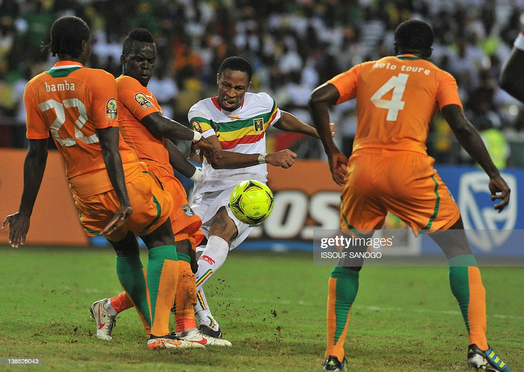 Ivory Coast's national football team players Bamba and Kolo Toure fight for the ball with Mali's Seydou Keita at the stade de l'amitie in Libreville...