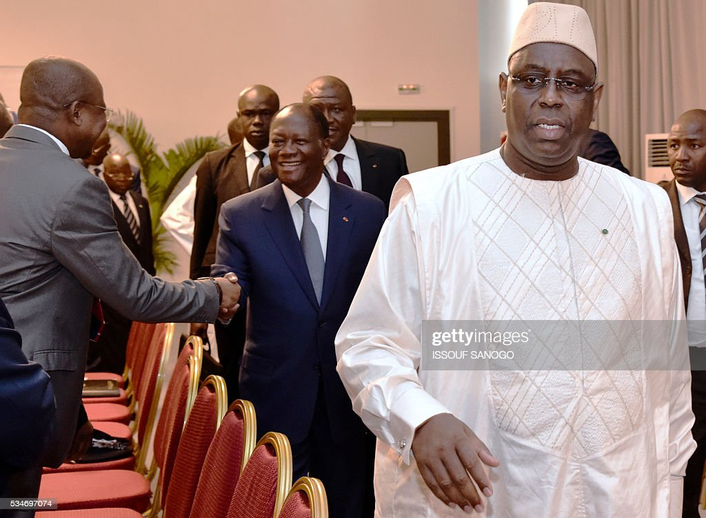 Ivory Coast's President Alassane Ouattara (C) and his Senegalese counterpart Macky Sall (R) walks during a security meeting of the ministers of Security Defence and Security of the West African Economic and Monetary Union zone (UEMOA) in Abidjan on May 27, 2016. / AFP / ISSOUF