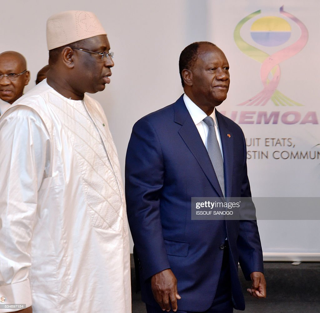 Ivory Coast's president Alassane Ouattara (R) and his Senegalese counterpart Macky Sall (L) walk together during a security meeting of the ministers of Security Defence and Security of the West African Economic and Monetary Union zone (UEMOA) in Abidjan on May 27, 2016 . / AFP / ISSOUF
