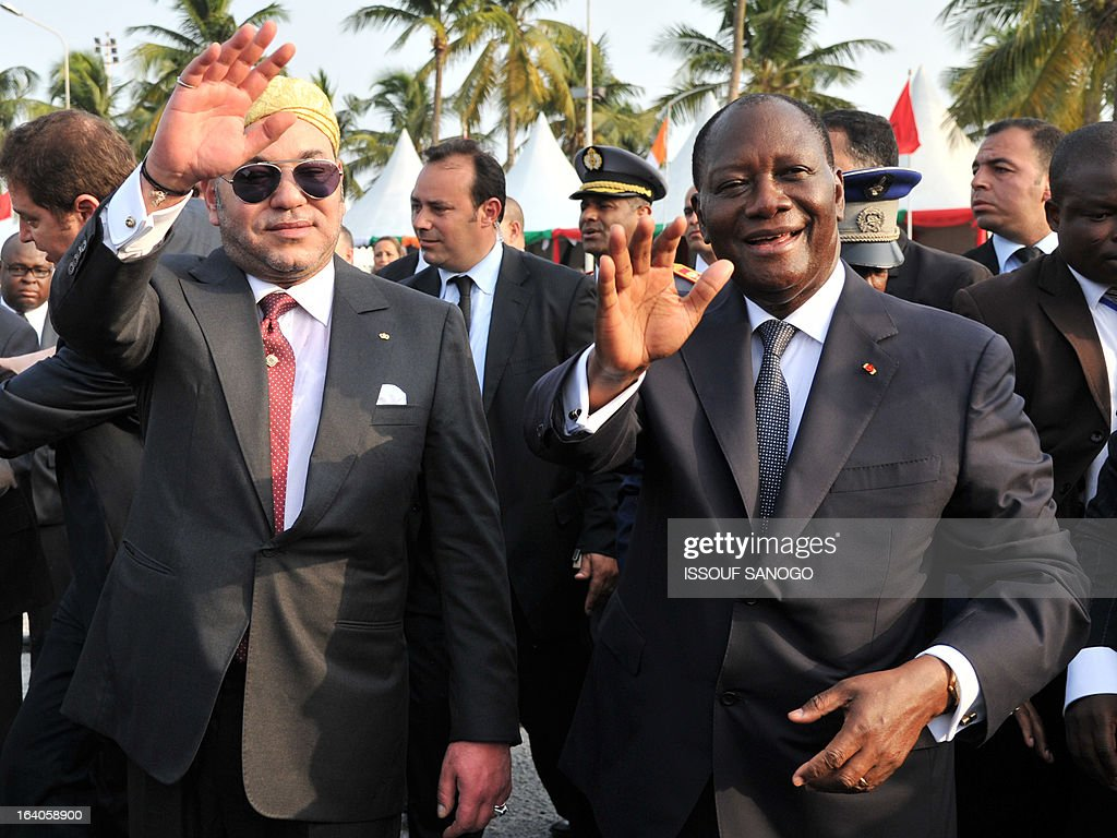 Ivory Coast's President Alassane Ouattara (R) and Moroccan King Mohammed VI (L) wave to the crowd during the King of Morocco's welcoming ceremony on March 19, 2013 at Abidjan airport. King Mohammed is on an official visit to Ivory Coast.