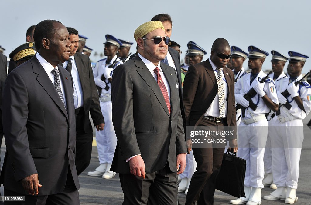 Ivory Coast's President Alassane Ouattara (l) and Moroccan King Mohammed VI (r) walk during the King of Morocco's welcoming ceremony on March 19, 2013 at Abidjan airport. King Mohammed is on an official visit to Ivory Coast.