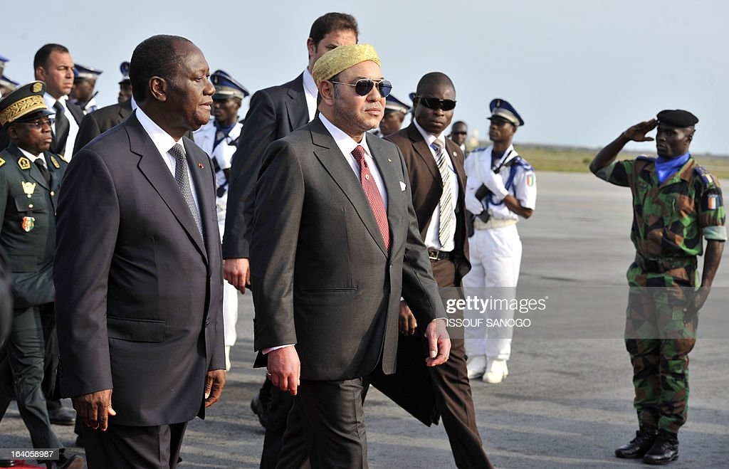 Ivory Coast's President Alassane Ouattara (l) and Moroccan King Mohammed VI (r) walk during the King of Morocco's welcoming ceremony on March 19, 2013 at Abidjan airport. King Mohammed is on an official visit to Ivory Coast. AFP PHOTO / ISSOUF SANOGO