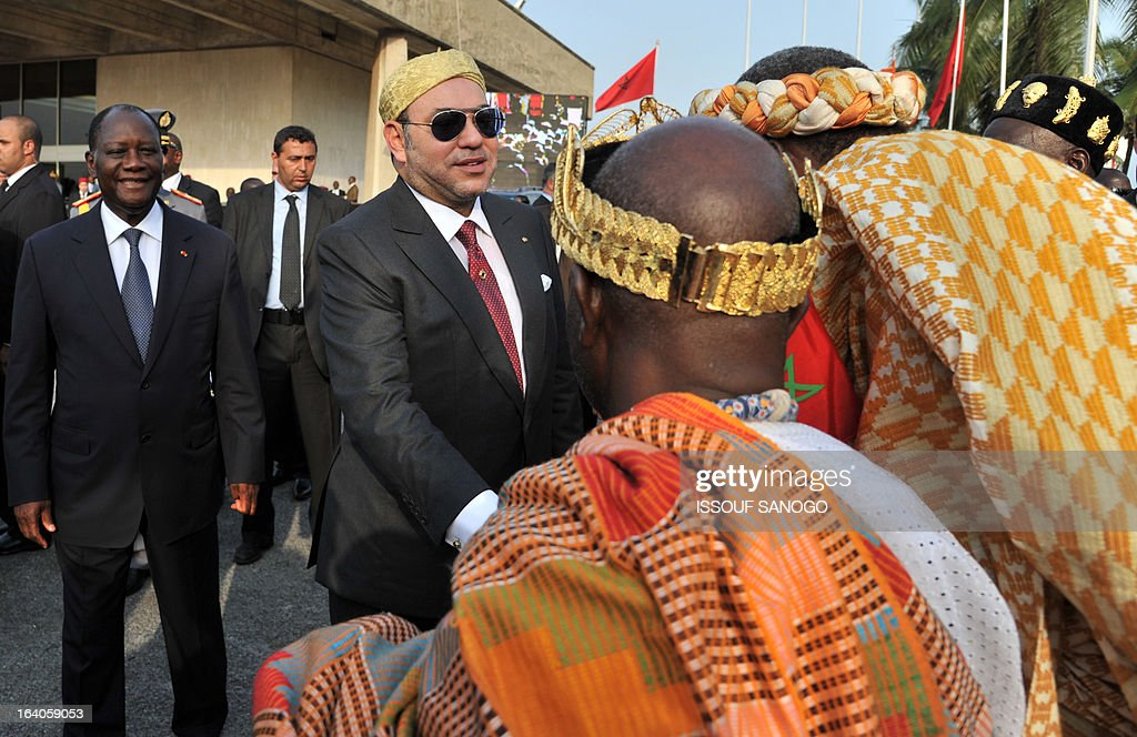 Ivory Coast's President Alassane Ouattara (l) and Moroccan King Mohammed VI (r) shake hands with traditional chiefs during the King of Morocco's welcoming ceremony on March 19, 2013 at Abidjan airport. King Mohammed is on an official visit to Ivory Coast.