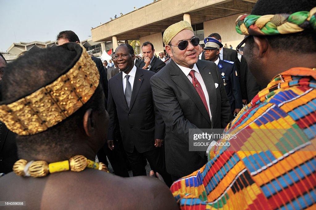 Ivory Coast's President Alassane Ouattara (l) and Moroccan King Mohammed VI (r) shake hands with traditional chiefs during the King of Morocco's welcoming ceremony on March 19, 2013 at Abidjan airport. King Mohammed is on an official visit to Ivory Coast. AFP PHOTO / ISSOUF SANOGO