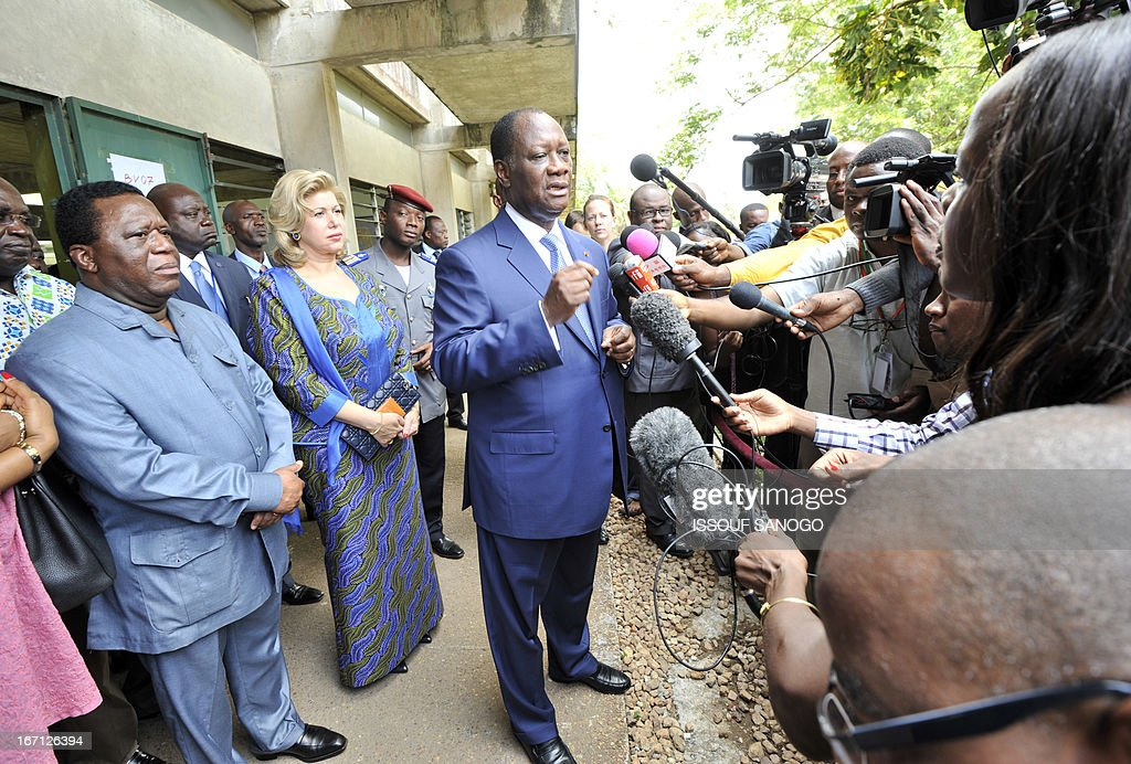 Ivory Coast's president Alassane Ouattara (C), flanked by first lady Dominique (2nd-L) and Youssouf Bakayoko (L), the President of Ivory Coast's Electoral Commission, speaks to media after cast her vote at the polling station on April 21, 2013 at the Lycee Sanite-Marie in Abidjan. Ivorians voted Sunday in local elections seen as a trial run for a presidential poll in 2015 amid high tensions as the party of former president Laurent Gbagbo boycotted the poll.