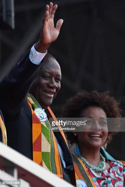 Ivory Coast's President Alassane Ouattara flanked by Francophonie's General Secretary Michaelle Jean waves at the audience as he arrives at the Felix...