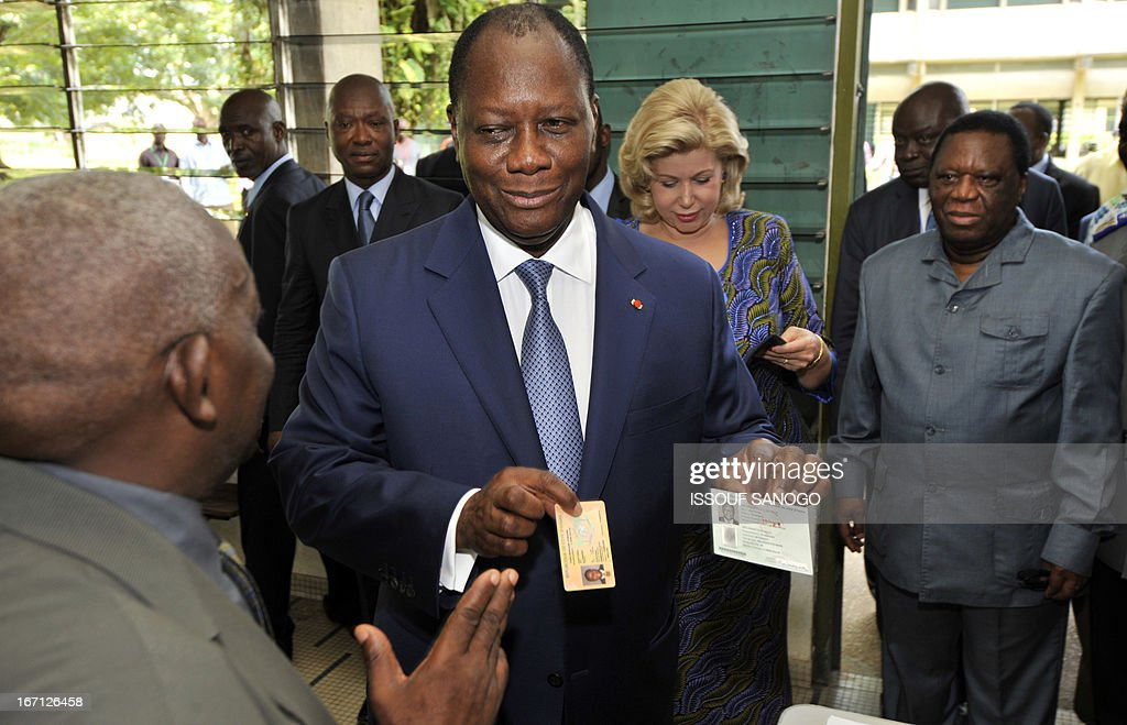 Ivory Coast's president Alassane Ouattara (2nd L), followed by First lady Dominique Ouattara (2nd R) and Youssouf Bakayoko (R), the president of Ivory Coast's Electoral Commission, shows his ID and voting cards as he arrives on April 21, 2013 at the Lycee Sainte-Marie polling station in Abidjan. Ivorians voted Sunday in local elections seen as a trial run for a presidential poll in 2015 amid high tensions as the party of former president Laurent Gbagbo boycotted the poll.
