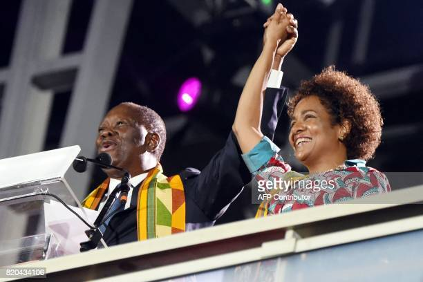 Ivory Coast's President Alassane Ouattara holds the hand of Francophonie's General Secretary Michaelle Jean as he delivers a speech at the Felix...