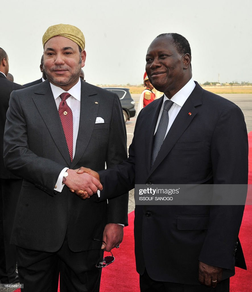 Ivory Coast's President Alassane Ouattara (R) poses with Moroccan King Mohammed VI (L) during the King of Morocco's welcoming ceremony on March 19, 2013 at Abidjan airport. King Mohammed is on an official visit to Ivory Coast.