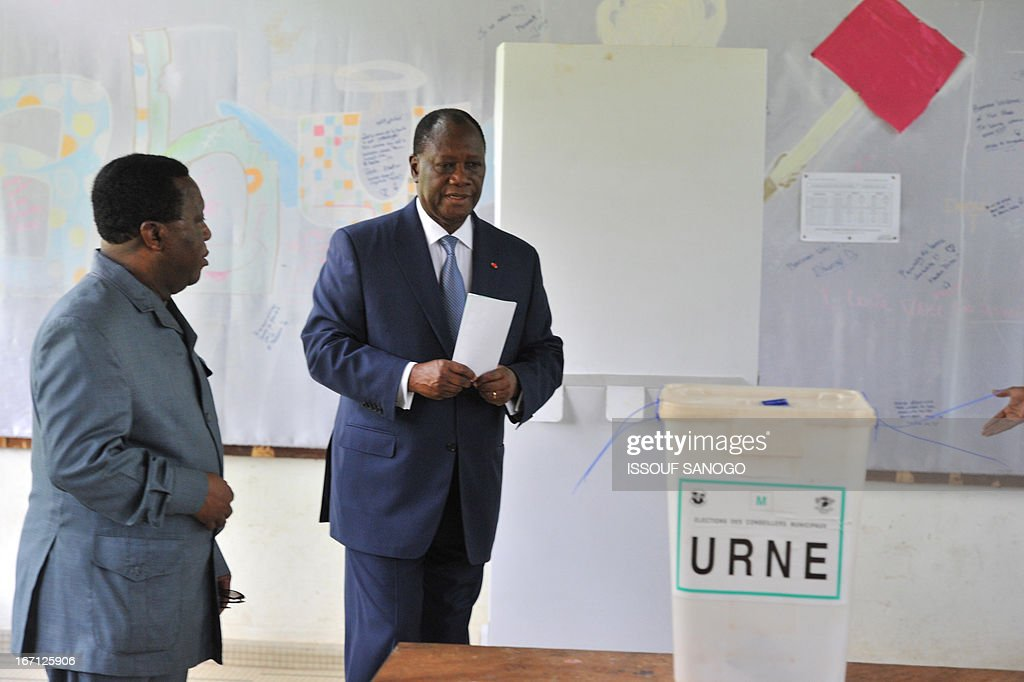 Ivory Coast's president Alassane Ouattara (R) prepares to cast his vote at a polling station of the Lycee Sainte-Marie in Abidjan on April 21, 2013 . Ivorians voted Sunday in local elections seen as a trial run for a presidential poll in 2015 amid high tensions as the party of former president Laurent Gbagbo boycotted the poll.