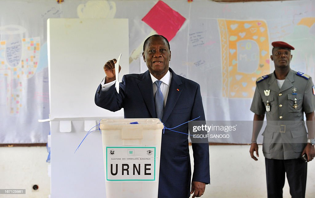 Ivory Coast's president Alassane Ouattara (L) prepares to cast his vote at a polling station of the Lycee Sainte-Marie in Abidjan on April 21, 2013 . Ivorians voted Sunday in local elections seen as a trial run for a presidential poll in 2015 amid high tensions as the party of former president Laurent Gbagbo boycotted the poll.