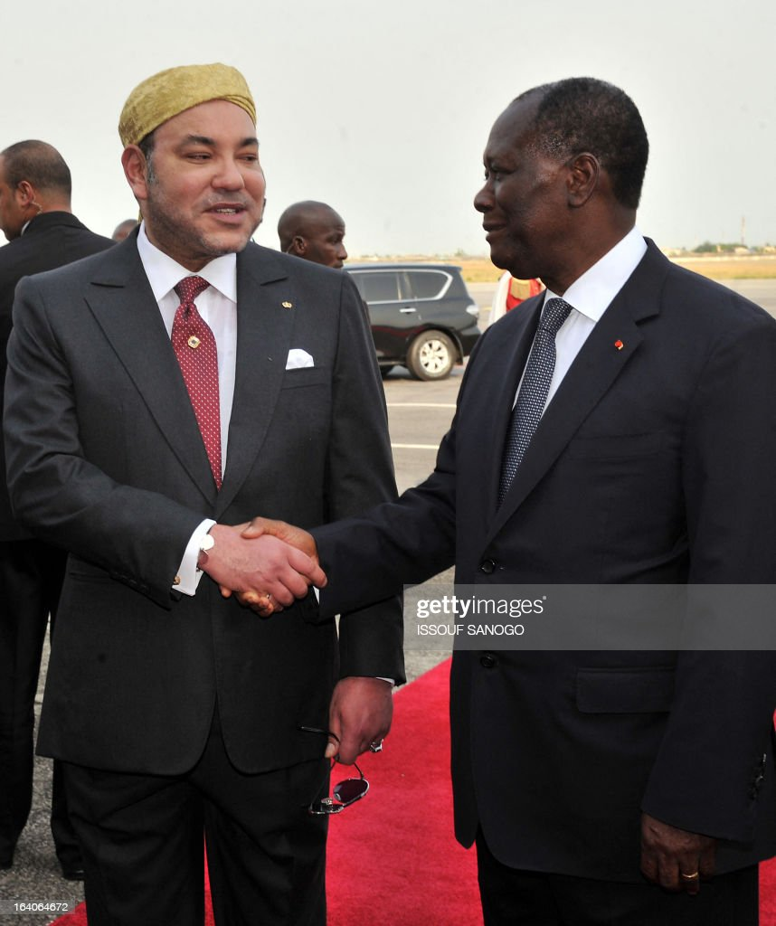 Ivory Coast's President Alassane Ouattara (R) shakes hand with Morocco's King Mohammed VI upon his arrival at Abidjan airport on March 19, 2013. King Mohammed is on an official visit to Ivory Coast.