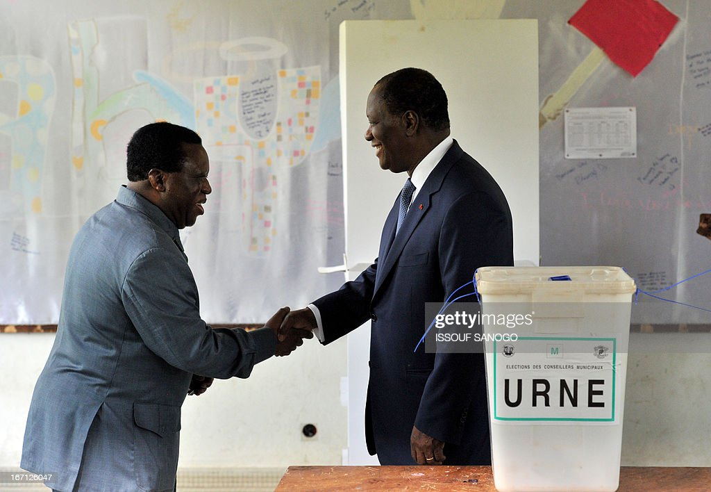 Ivory Coast's president Alassane Ouattara (R) shakes hands with Youssouf Bakayoko (L), the president Ivory Coast's Electoral Commission, after casting his vote at a polling station of the Lycee Sainte-Marie in Abidjan on April 21, 2013 . Ivorians voted Sunday in local elections seen as a trial run for a presidential poll in 2015 amid high tensions as the party of former president Laurent Gbagbo boycotted the poll. AFP PHOTO / ISSOUF SANOGO