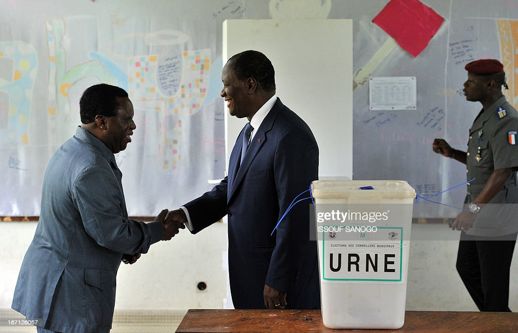 Ivory Coast's president Alassane Ouattara (R) shakes hands with Youssouf Bakayoko (L), the president Ivory Coast's Electoral Commission, after casting his vote at a polling station of the Lycee Sainte-Marie in Abidjan on April 21, 2013 . Ivorians voted Sunday in local elections seen as a trial run for a presidential poll in 2015 amid high tensions as the party of former president Laurent Gbagbo boycotted the poll.