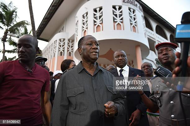 Ivory Coast's president Alassane Ouattara speaks to the press outside the Etoile du Sud one of the hotel attacked by heavily armed men on March 13...