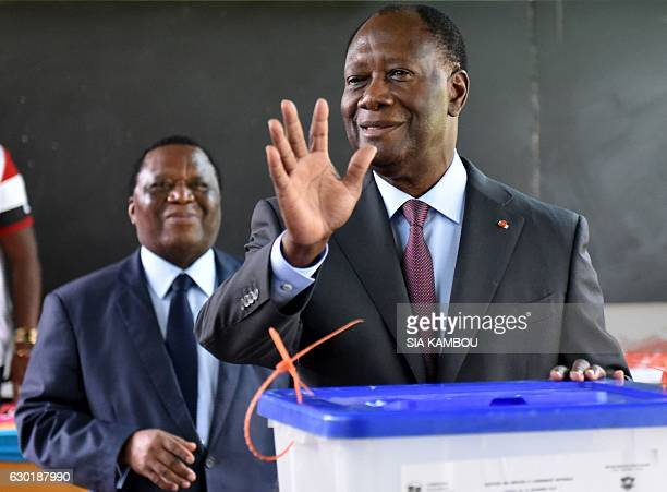 Ivory Coast's President Alassane Ouattara waves after casting his ballot into an urn next to the President of the Independent Election Commission...