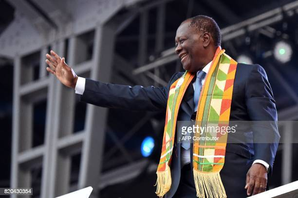 Ivory Coast's President Alassane Ouattara waves at the audience as he arrives at the Felix HouphouetBoigny stadium in Abidjan during the opening...