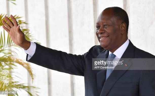 Ivory Coast's president Alassane Ouattara waves at the presidential palace on July 14 2017 in Abidjan SANOGO