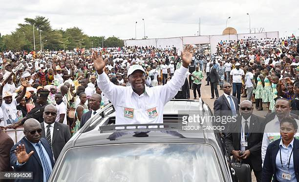 Ivory Coast's president and candidate for the upcoming presidential election Alassane Ouattara waves at supporters on October 9 2015 in Yamoussoukro...