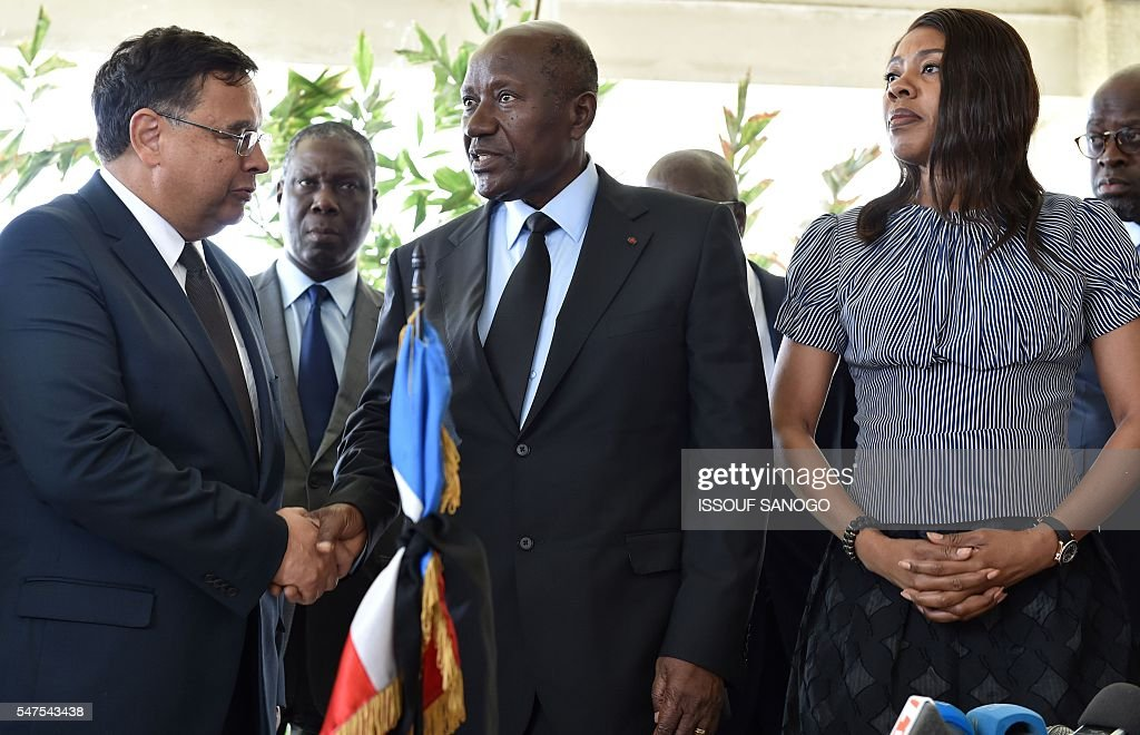 Ivory Coast's Prime Minister Daniel Kablan Duncan shakes hands with French ambassador in Abidjan Georges Serre flanked by Ivory Coast's Minister of...