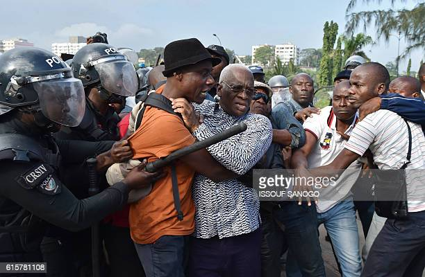 TOPSHOT Ivory Coast's riot police arrest Aboudramane Sangare one of country's opposition leaders during a protest against a referendum on the...
