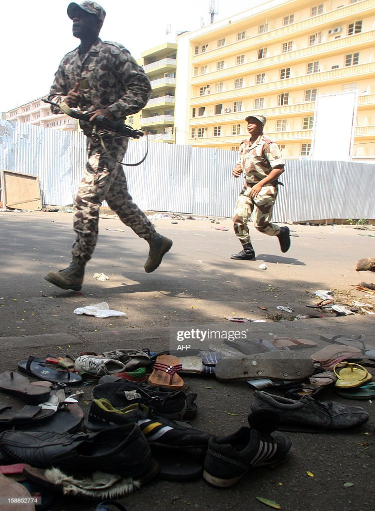 Ivory Coast's soldiers run in a street as shoes are scattered on the pavement at the scene of a stampede in Abidjan, on January 1, 2013. At least 61 people died and dozens more were injured in Abidjan as crowds that had gathered for celebratory New Year's fireworks stampeded overnight, Ivory Coast rescue workers said on January 1, 2013.