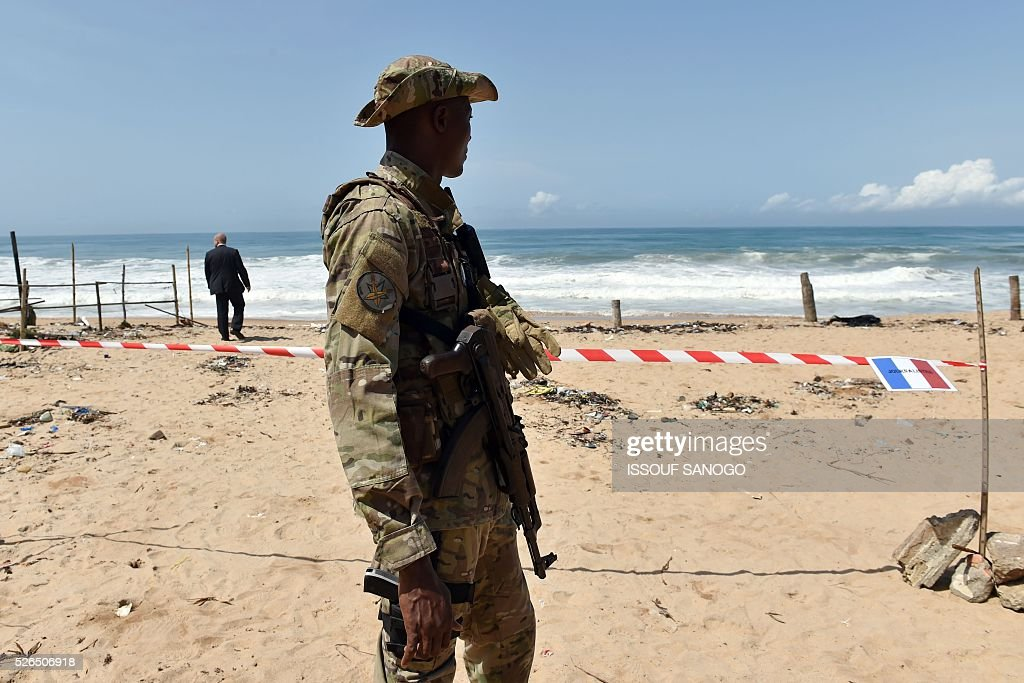Ivory Coast's special forces officer stands guard as he waits, on April 30, 2016, for the arrival of French Defence Minister Jean-Yves Le Drian at the Grand-Bassam beach by the Hotel Etoile du Sud to pay a tribute to the 19 victims of the jihadist attack of March 13. France will increase the number of its troops in Ivory Coast, Defence Minister Jean-Yves Le Drian said on April 29 on a trip to the African nation which hosts a regional base for French forces. / AFP / ISSOUF
