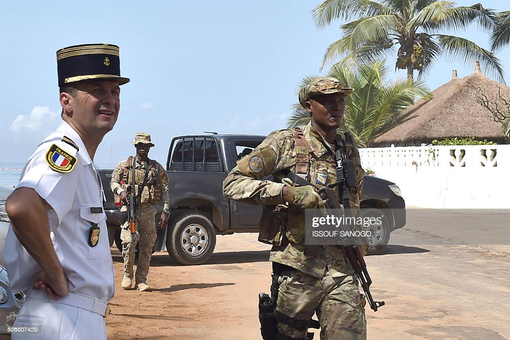 Ivory Coast's special forces officer walks past a French army officer on April 30, 2016, before the arrival of French Defence Minister Jean-Yves Le Drian at the Grand-Bassam beach by the Hotel Etoile du Sud to pay a tribute to the 19 victims of the jihadist attack of March 13. France will increase the number of its troops in Ivory Coast, Defence Minister Jean-Yves Le Drian said on April 29 on a trip to the African nation which hosts a regional base for French forces. / AFP / ISSOUF