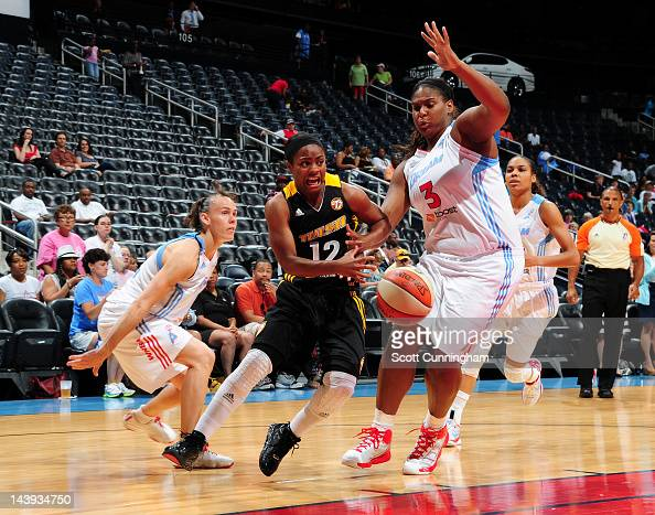 Ivory Latta of the Tulsa Shock drives against Courtney Paris and Coco Miller of the Atlanta Dream at Philips Arena on May 4 2012 in Atlanta Georgia...