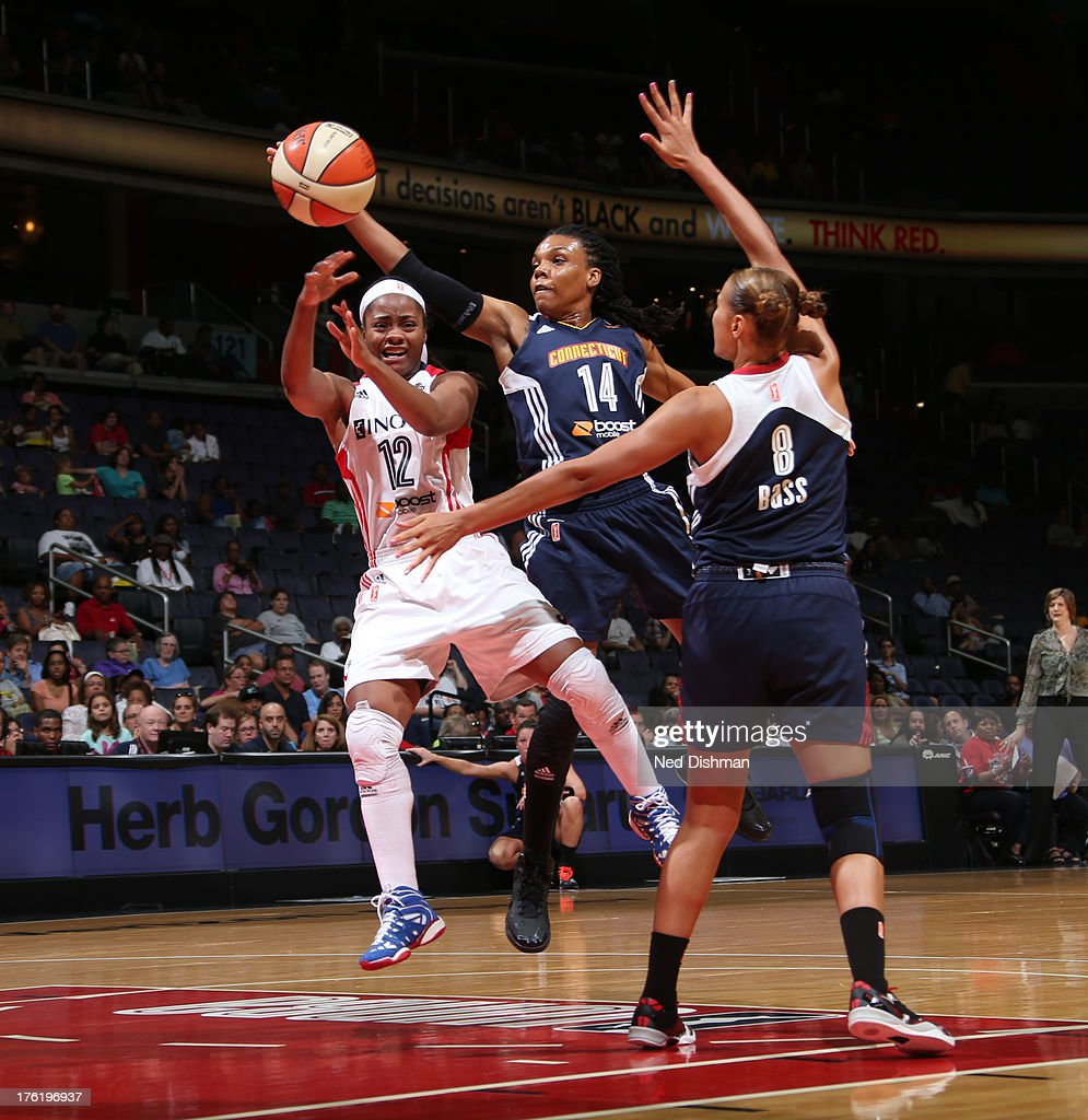 Ivory Latta of the Washington Mystics passes against Tan White of the Connecticut Sun at the Verizon Center on August 11 2013 in Washington DC NOTE...