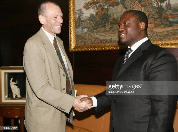 Ivory's Coasts Prime Minister Guillaume Soro shakes hands with International Monetary Fund Representative Arend Kouwenaar in Abidjan on February 28...