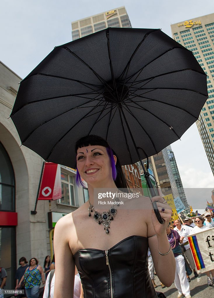Ivy Berlin, under a black umbrella, walks in the march. Pride Toronto Dyke March works its way through the downtown core as marchers celebrate Pride Toronto festivities, on Saturday, June 29, 2013. The larger extravaganza of the Pride Parade is set for Sunday.