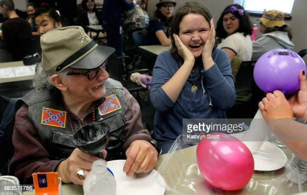 Ivy Weiderman right and Gregory Brown laugh aloud as baking soda sprays out from a balloon during a science experiment The two are with a group of...