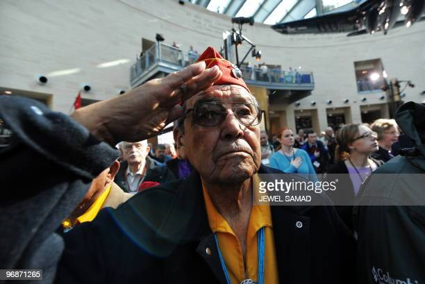Iwo Jima veteran Frank Willetto salutes as the Marine Corp band play the national anthem during a ceremony commemorating the 65th Anniversary of the...