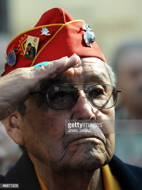 Iwo Jima veteran Frank Willetto salutes as the Marine Corp band plays the National Anthem during a ceremony commemorating the 65th Anniversary of the...